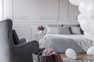 Trendy bedroom design with elegant double bed with grey sheets,