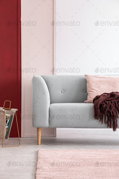 Newspaper rack next to grey couch in bright living room interior