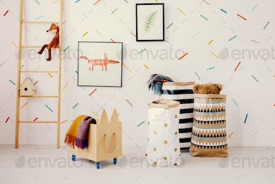 Wooden crate and patterned bags in child's room interior with fo