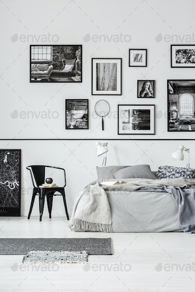 Rugs and black chair next to bed in white bedroom interior with