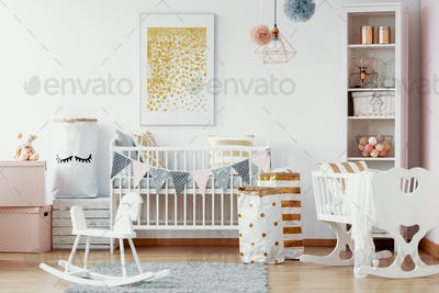 Wooden rocking horse, white and gold paper bags and white wooden