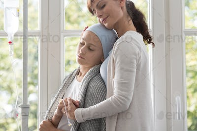 Caregiver hugging sick child with cancer wearing headscarf