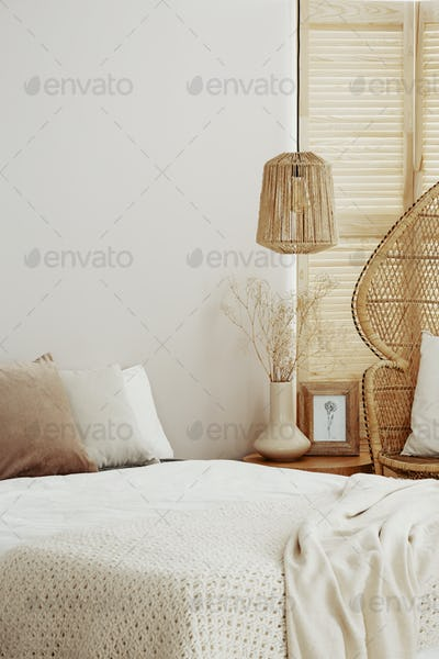 Rattan chandelier above bed in natural bedroom, copy space on em