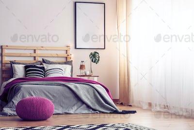 Mockup in black frame on empty wall of bright scandinavian bedro