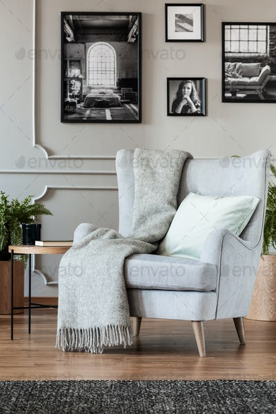 Comfortable grey armchair with cozy blanket and pillow in trendy