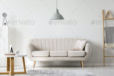 Grey lamp above pillow on white sofa next to wooden coffee table