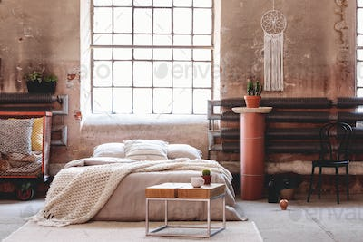 Wooden table in front of bed with blanket in wabi sabi bedroom i