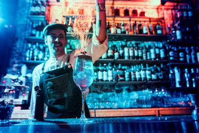 Glass of fiery cocktail on the bar counter against the background of bartenders hands with fire