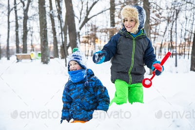 Two Happy child boy playing snowballs outdoor.