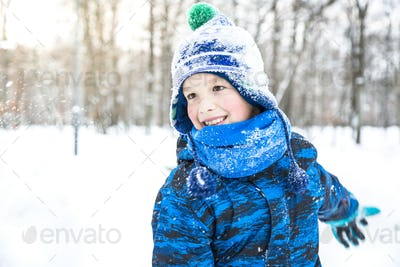 Happy child boy playing snowballs outdoor.