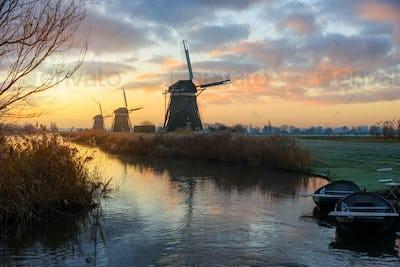 Windmills at sunrise in a rural dutch landscape