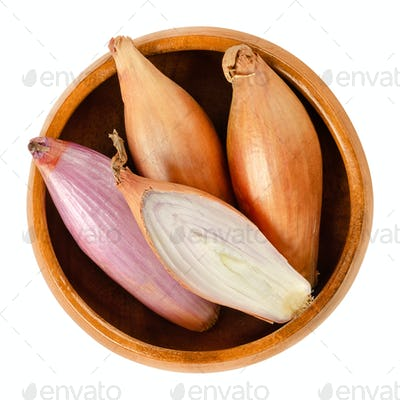 Long shallots, whole and sliced, in wooden bowl over white