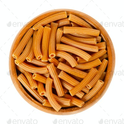 Chickpea pasta, brown Sedanini Rigati, in wooden bowl over white.