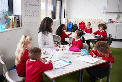 Young female infant school teacher sitting at a table in a classroom with her pupils