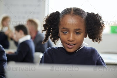 Young black schoolgirl using a laptop computer sitting at desk in a primary school classroom