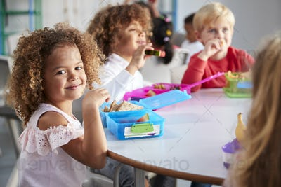 Close up of smiling young children sitting at a table eating their packed lunches together