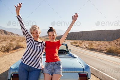 Mum and adult daughter on road trip stand waving to camera