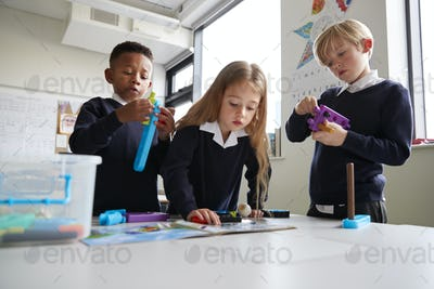 Three primary school children working together with toy construction blocks in a classroom