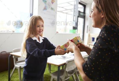 Schoolgirl at a primary school presenting a gift to her female teacher in a classroom, close up