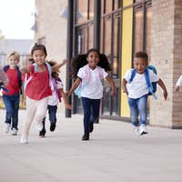 Smiling multi-ethnic school kids running in a walkway outside their infant school building