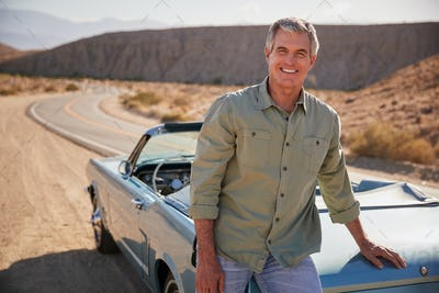 Senior white man leaning on open top car at desert roadside