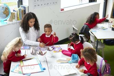 Elevated view of female kindergarten teacher sitting at a table helping four children