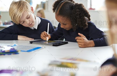Schoolgirl using a tablet and stylus sitting with a boy at a desk in a primary school