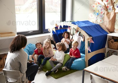 Female infant school teacher sitting on a chair showing a book to a group of children