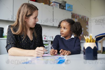 Young female primary school teacher working one on one with a schoolgirl at a table in a classroom