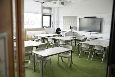 An empty classroom in a primary school with white desks and chairs, seen from doorway