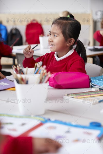 Chinese schoolgirl wearing school uniform sitting at a desk in a classroom