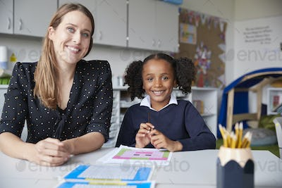 Young female primary school teacher and schoolgirl working one on one in a classroom
