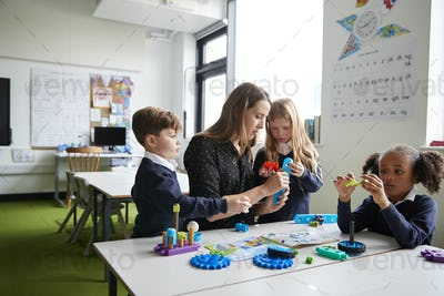 Female primary school teacher in a classroom working with construction toys