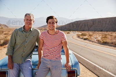 Father and adult son on road trip leaning against their car