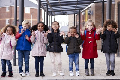 A group of smiling young multi-ethnic school kids standing in  walkway outside their infant school