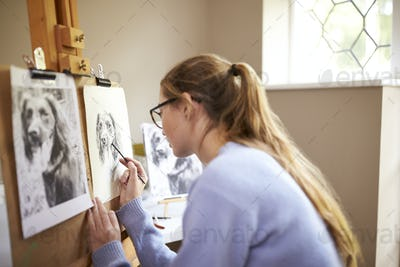 Side View Of Female Teenage Artist Sitting At Easel Drawing Picture Of Dog in Charcoal