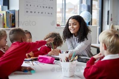 Smiling female infant school teacher sitting at a table in the classroom with schoolchildren