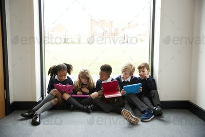 Primary school kids in front of a window in a school corridor looking at tablet computers