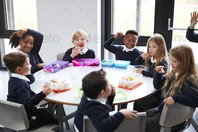 Elevated view of primary school kids sitting together at a round table eating their packed lunches