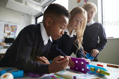 Close up of three primary school children working together with toy construction blocks