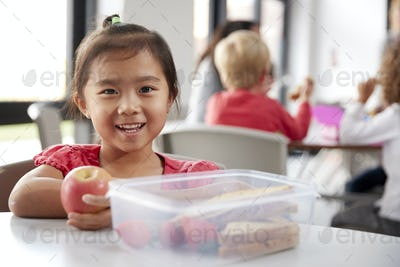 Young Chinese schoolgirl sitting at a table during her lunch break at kindergarten, smiling