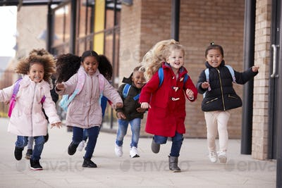 Happy young school girls wearing coats and carrying schoolbags running in a walkway