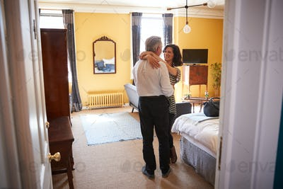Mature couple embrace, looking at each other, in hotel room