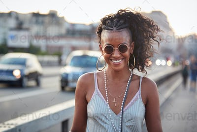 Trendy woman in striped camisole and sunglasses, portrait