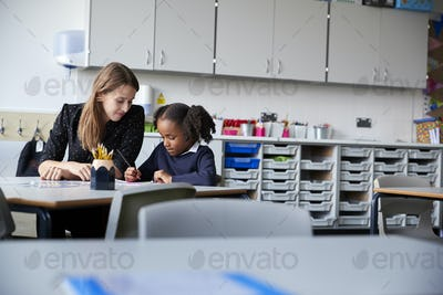Female primary school teacher working one on one with a schoolgirl sitting at table in a classroom