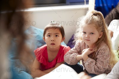 Two infant school girls sitting on bean bagslistening to their teacher reading a story