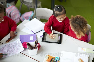 Two infant school girls sitting at a table, using a tablet computer and stylus in a classroom