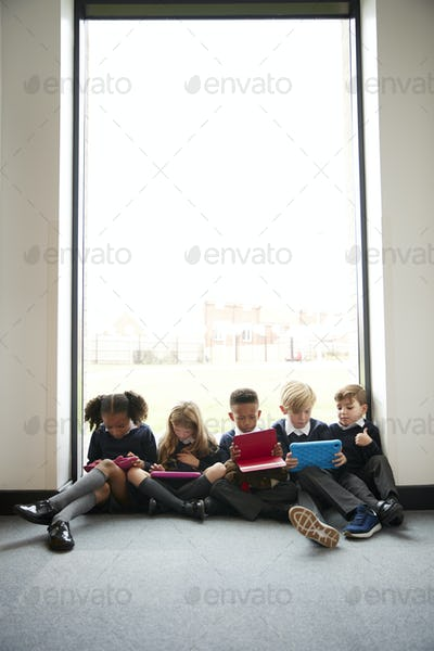 Primary school kids sitting in front of a window in a school corridor using tablet computers