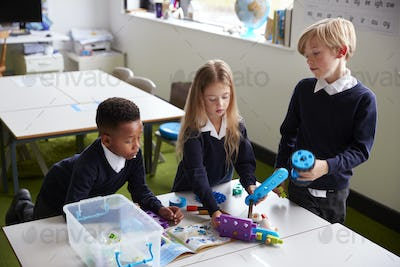 Elevated view of three primary school kids working together with toy construction blocks