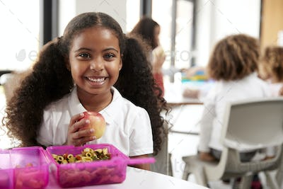 Young black schoolgirl smiling and holding an apple in a kindergarten during lunch